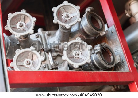 Firefighting equipment on red fire truck. Water hydrants closeup photo with selective focus - stock photo