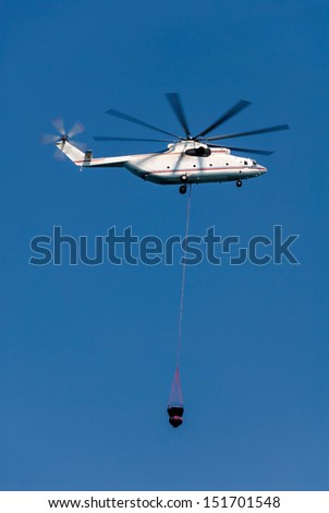 Firefighting helicopter flying towards the fire, with the container full of water, hanging far below. - stock photo