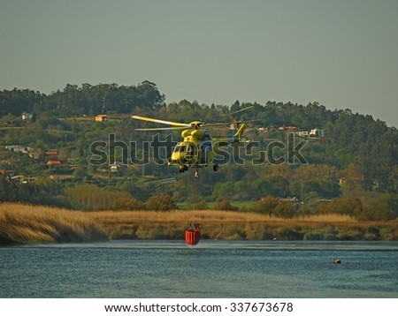 Firefighting helicopter taking water from a river - stock photo
