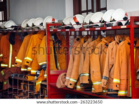 Firefighting safety equipment, including helmets, flame-resistant jackets and boots, arranged on a rack at the Georgetown Fire Station. - stock photo
