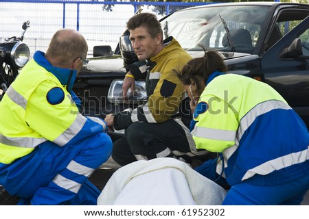 fireman and paramedic discussing the course of action,  carrying for an woman ad the side of a car crash
