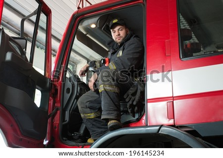 Fireman behind steering wheel of a firefighting truck  - stock photo