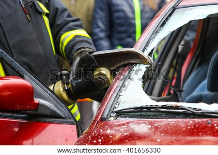 Fireman breaks the car's window. Fireman working in the car accident. Close up shot