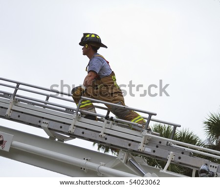 fireman climbing a ladder to enter a building