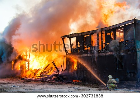 Fireman extinguishes a burning old wooden residential house - stock photo