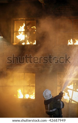 Fireman fighting a fire. The burning man jumps from a window of the second floor. - stock photo