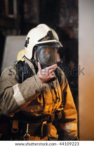 Fireman in fire protection suit and mask - stock photo