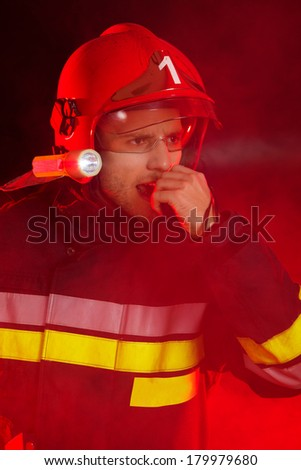 Fireman in smoke using walkie-talkie and looking away. - stock photo