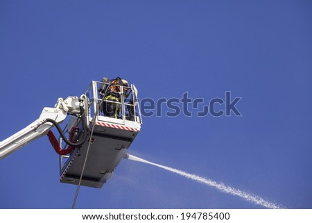 Fireman on an extended boom fighting a fire with a water hose  - stock photo