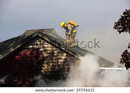 Fireman on the roof of an abandoned  burning house - stock photo