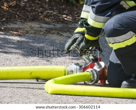Fireman operating the valve of a firehose - stock photo