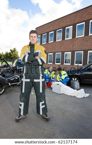 Fireman posing in his flame resistant coveralls in front of an accident site - stock photo