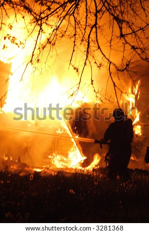 Fireman putting out a huge house fire in the city of Detroit - stock photo