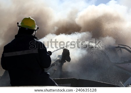 Fireman spraying water on a burnt out and smoking vehicle