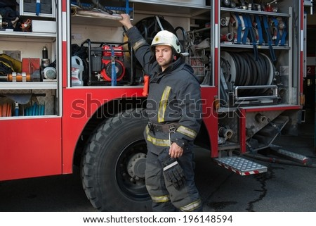 Fireman taking equipment from firefighting truck  - stock photo