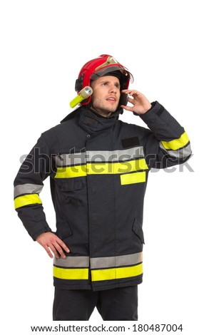 Fireman using smart phone and looking away. Three quarter length studio shot isolated on white. - stock photo