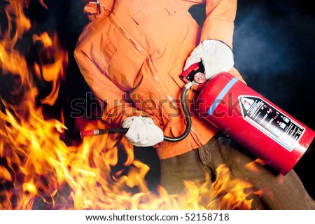 fireman with extinguisher fighting a fire - stock photo