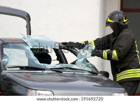 Fireman with protective overalls and work gloves while breaking a car windshield to release the people injured after car accident - stock photo