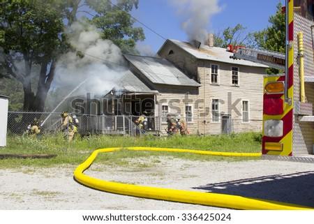 Firemen Battle a House Fire. - stock photo
