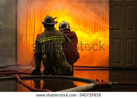 Firemen fighting a flames of burning fire, fireman training - stock photo