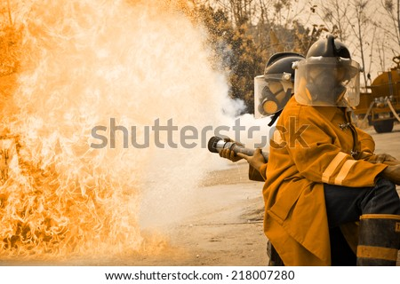 Firemen in action fighting fire during training - stock photo