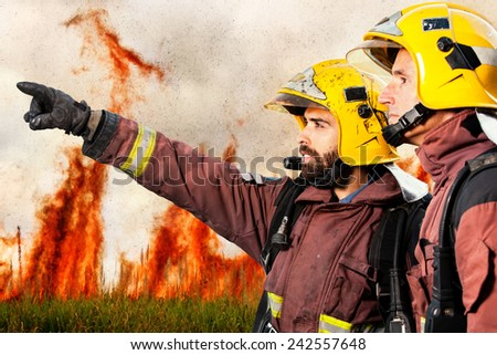 Firemen looking and pointing at danger situation with high flames in background. - stock photo