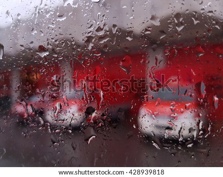 Firemen's tears abstract: fire engines at a fire station in the rain from behind a glass covered in raindrops background - stock photo