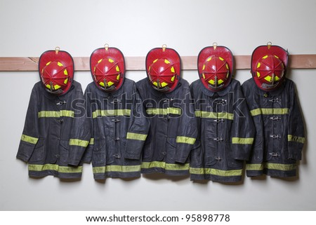 Firemen suits and helmets hanging inside a room - stock photo