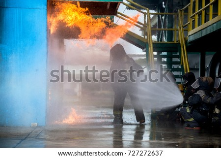 Firemen using water from hose for fire fighting at firefight training of insurance group. Firefighter wearing a fire suit for safety under the danger case.