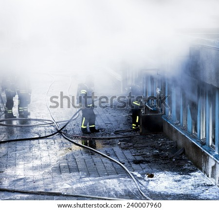 Firemen working to extinguish fire in building - stock photo