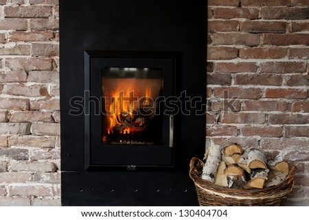 Fireplace in a brick wall and woods in basket