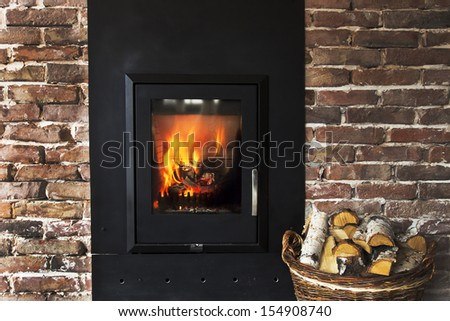 Fireplace in a brick wall and woods in basket - stock photo