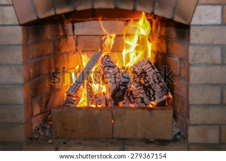 Fireplace in the house. Firewood burns in a fireplace. A fireplace in a country house - stock photo