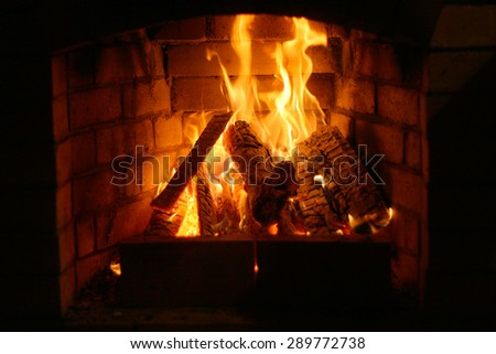 Fireplace in the house. Firewood burns in a fireplace. A fireplace in a country house