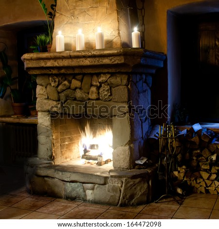 Fireplace room. Chimney place, candles and woodpile. Vintage interior - stock photo