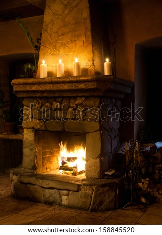 Fireplace room. Chimney place, candles and woodpile. Vintage style classic interior. - stock photo
