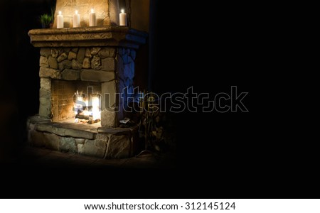 Fireplace room. Chimney place with candles and real fire and flame. Vintage style interior. Copy space, black background - stock photo