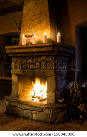 Fireplace room romantic interior. Chimney place, candles and woodpile. Vintage style classic room.