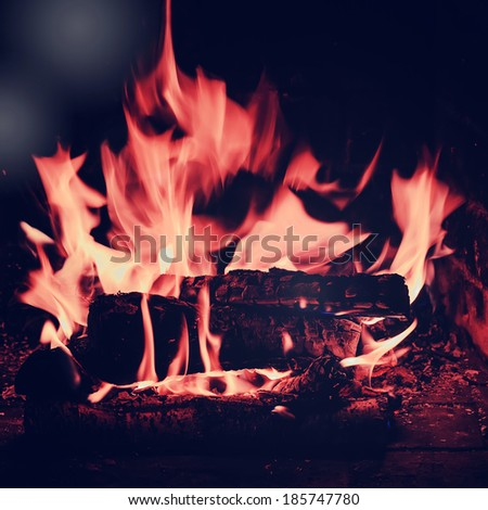 Fireplace with birch firewood and flame with retro filter effect.  - stock photo