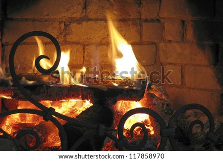 Fireplace with burning logs and designed barrier in the foreground - stock photo