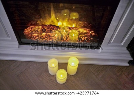 Fireplace with burning woods inside and candles on the floor. - stock photo
