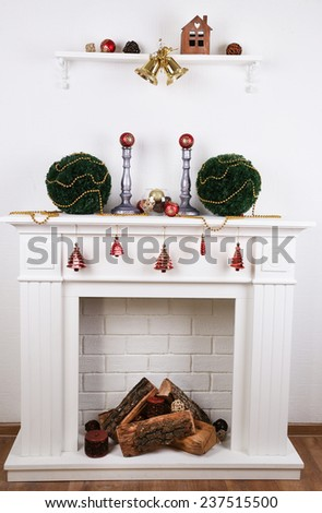 Fireplace with Christmas decoration on wooden floor near white background - stock photo