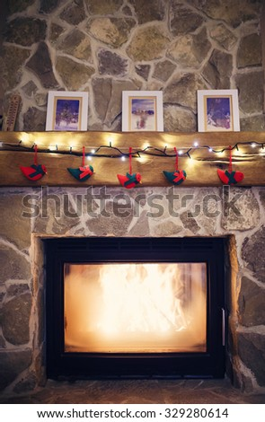 Fireplace with christmas decorations and a light chain - stock photo