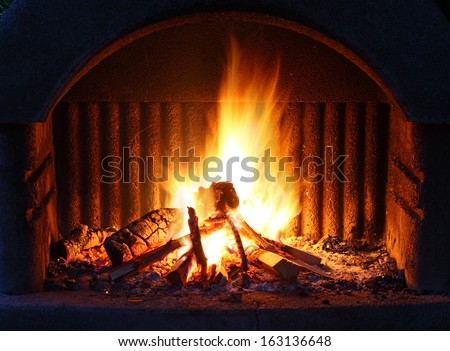 Fireplace with fire at night - outdoor shot - stock photo