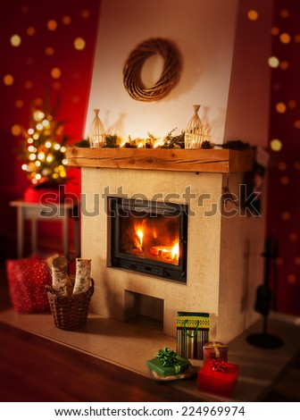 Fireplace with gifts, christmas tree and lights on red background. Warm and cozy home interior decoration, rustic or country style. - stock photo