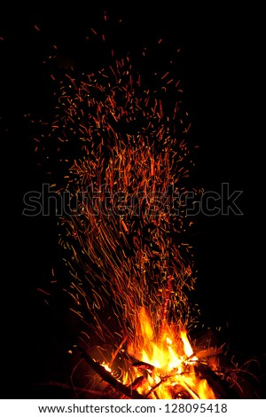 Fireplace with sparks in dark mountains - stock photo