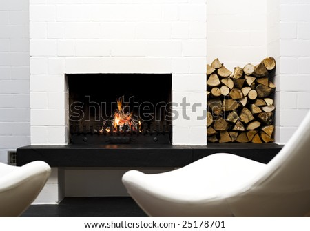 fireplace with stacked wood, lounge chairs in front - stock photo