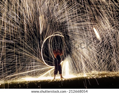 Firestarter performing amazing fire show with sparkles in the night - stock photo