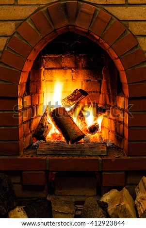 firewood and tongues of fire in fireplace in country cottage - stock photo