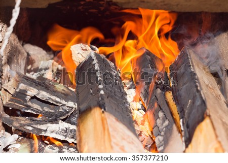 Firewood blaze in rural stove from brick.Alternative energy source background - stock photo